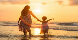 a mother and daughter walk in the sea towards a sunset