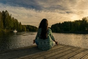 A woman meditates looking out over some water